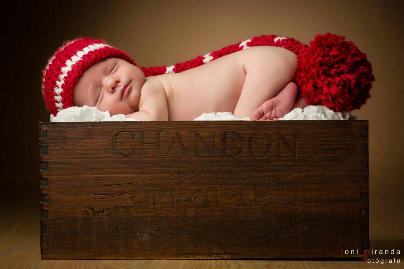 recién nacida en caja de madera y gorrito