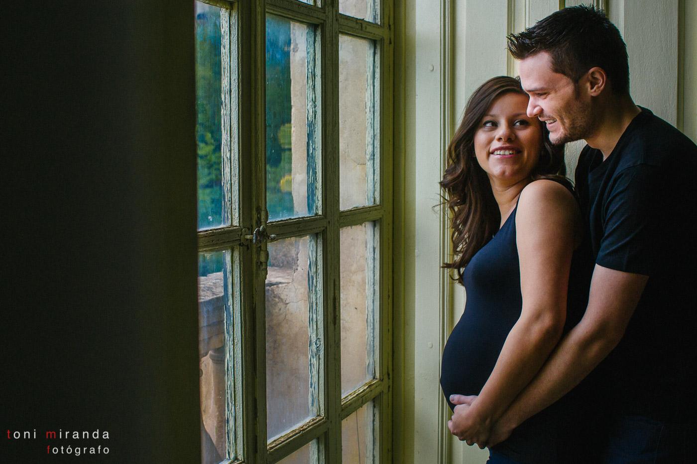 embarazada con su pareja frente a la ventana de casa noble de Alcoy