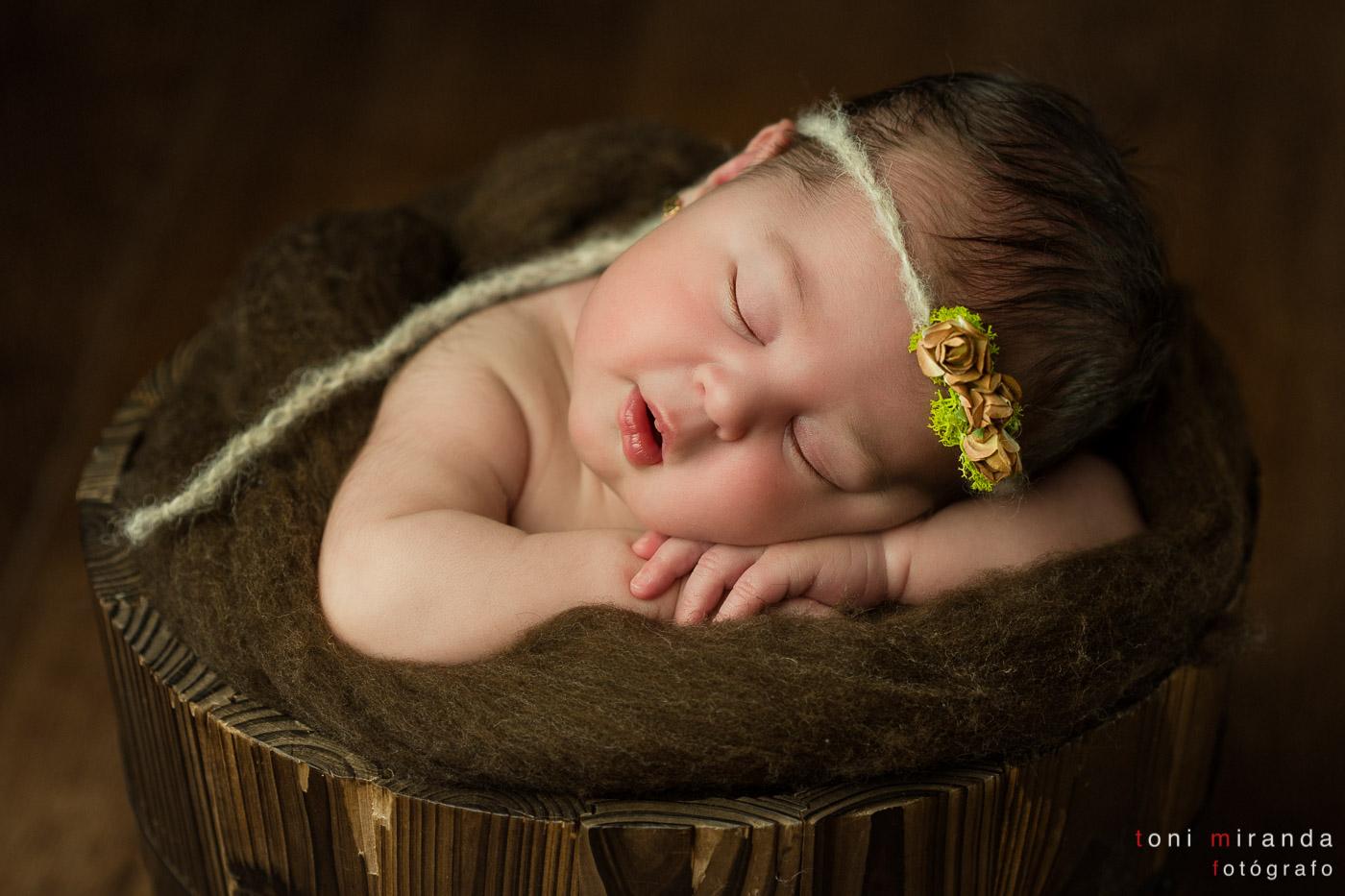 bebe recién nacida dentro de cubo de madera