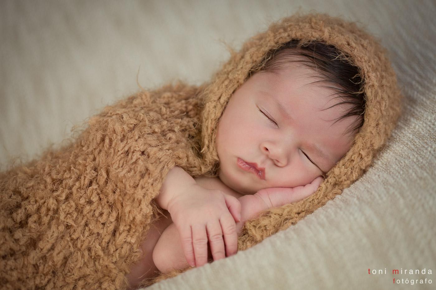 bebe recien nacido durmiendo liado en manta de algodon