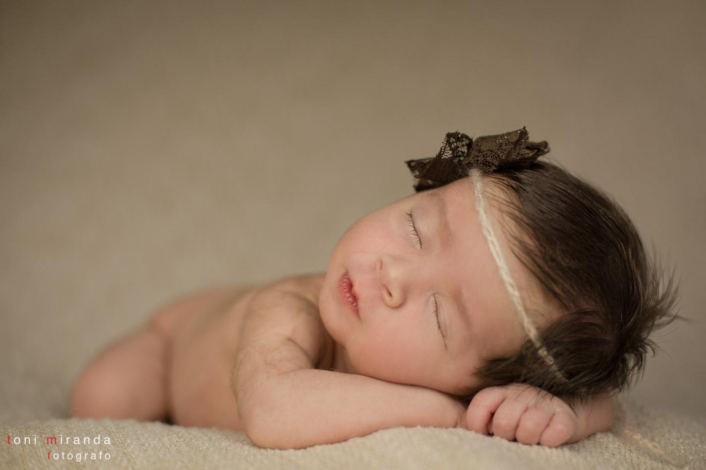 bebe recien nacido durmiendo en manta con lazo en la cabeza