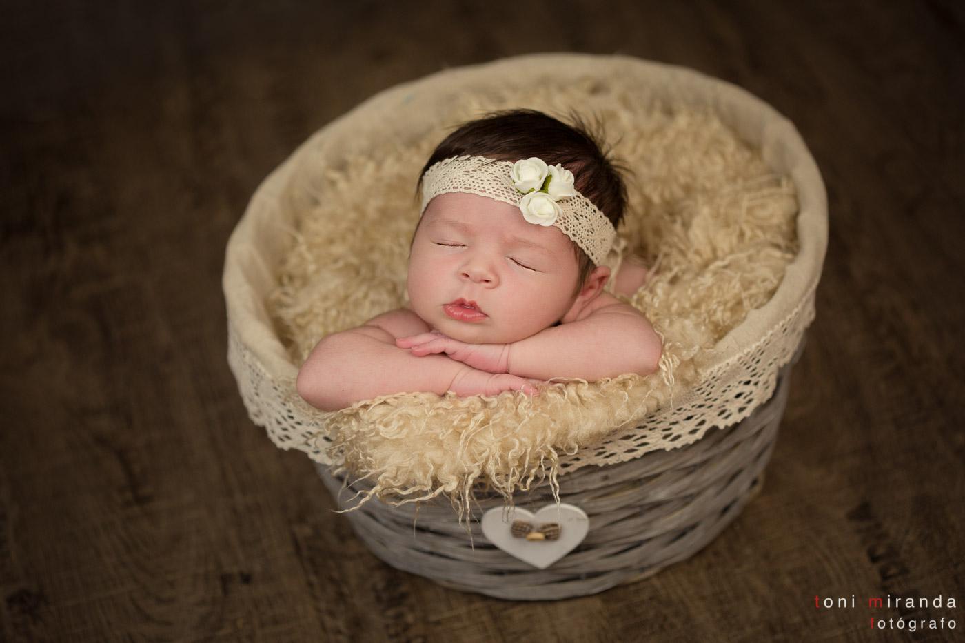 bebe recien nacido durmiendo en cesta con florecitas en la cabeza