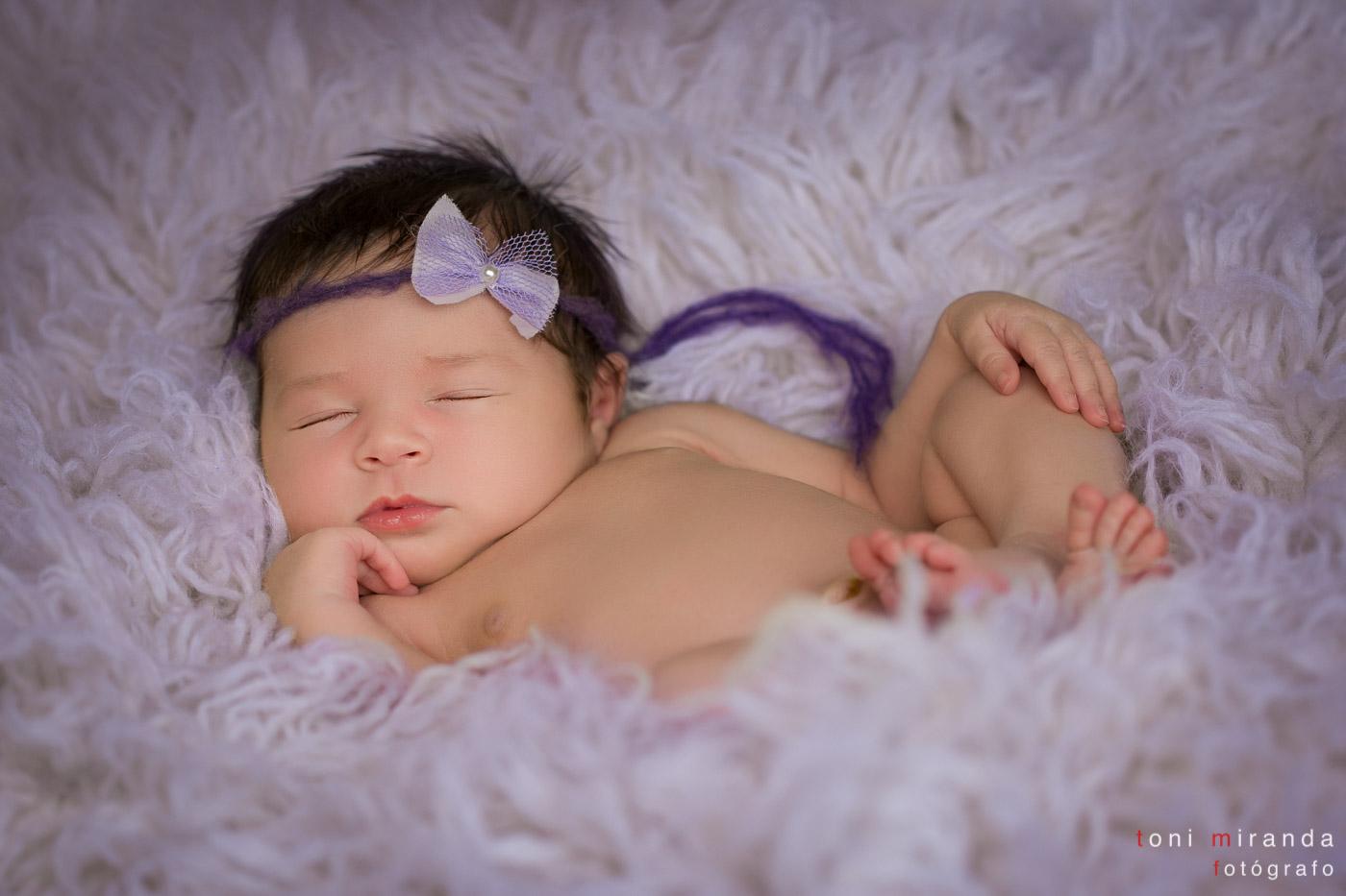 bebe recien nacido durmiendo sobre manta con lacito lila y mano en barbilla