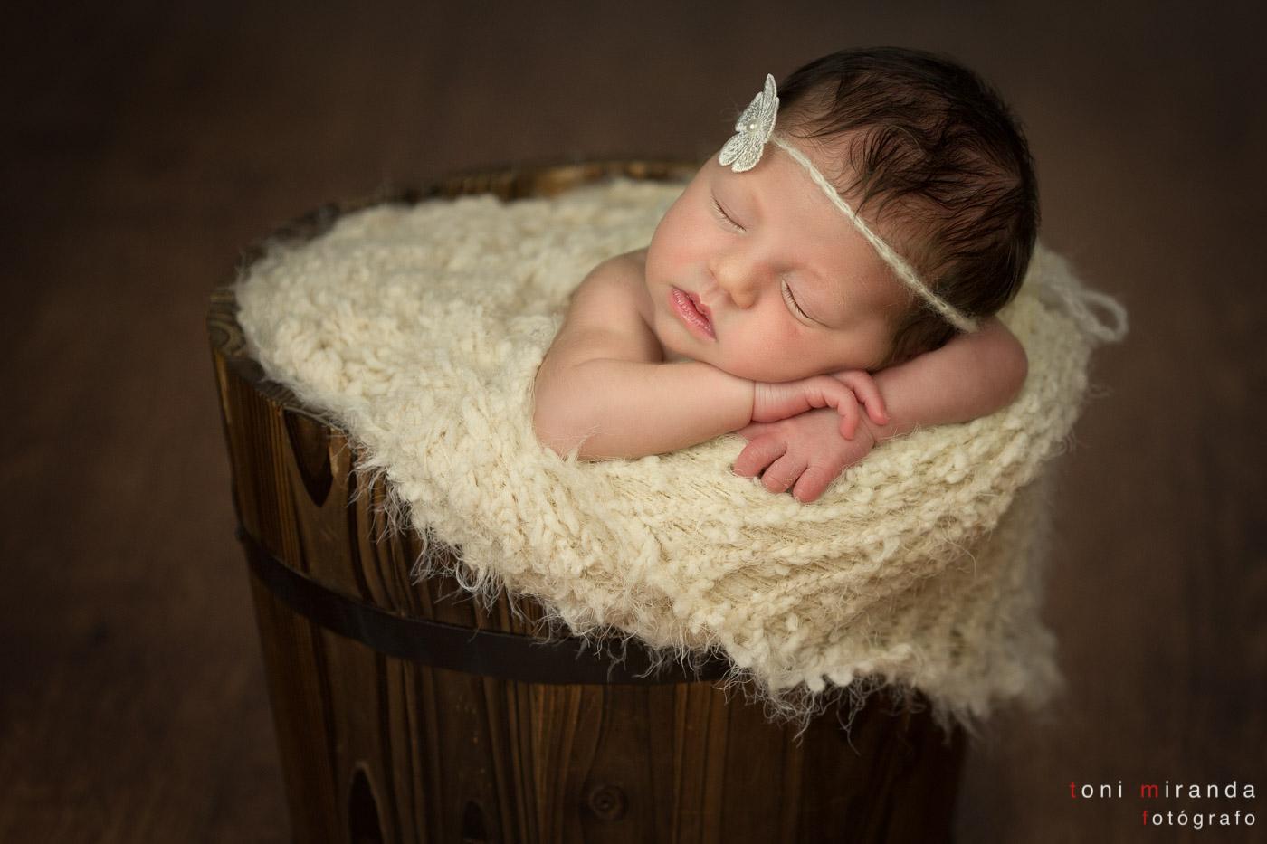 recién nacida durmiendo en cubo de madera con lazo en la cabeza