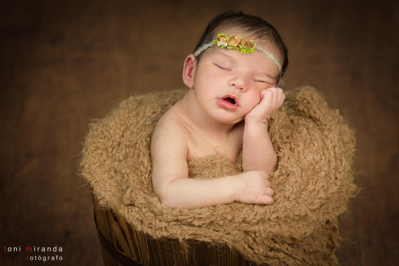bebe recien nacido durmiendo en cubo de madera apoyado en sus manos con florecitas en la cabeza