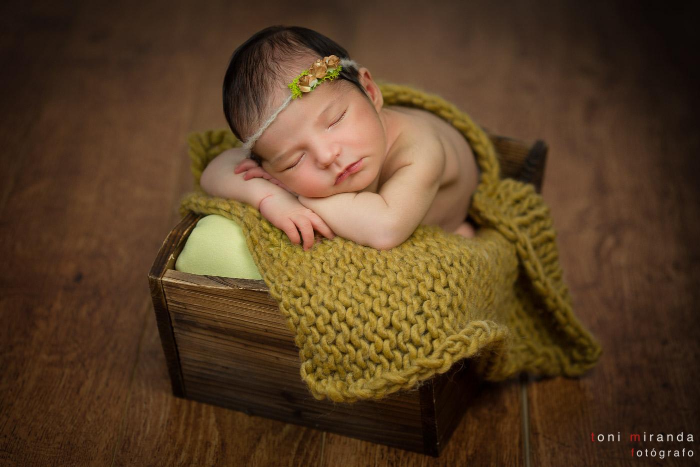 bebe recien nacido durmiendo en caja de madera con flores en la cabeza
