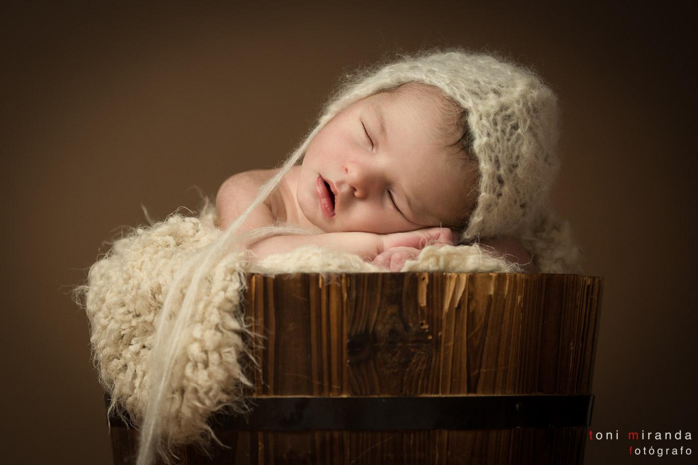 newborn en cubo con prop durmiendo