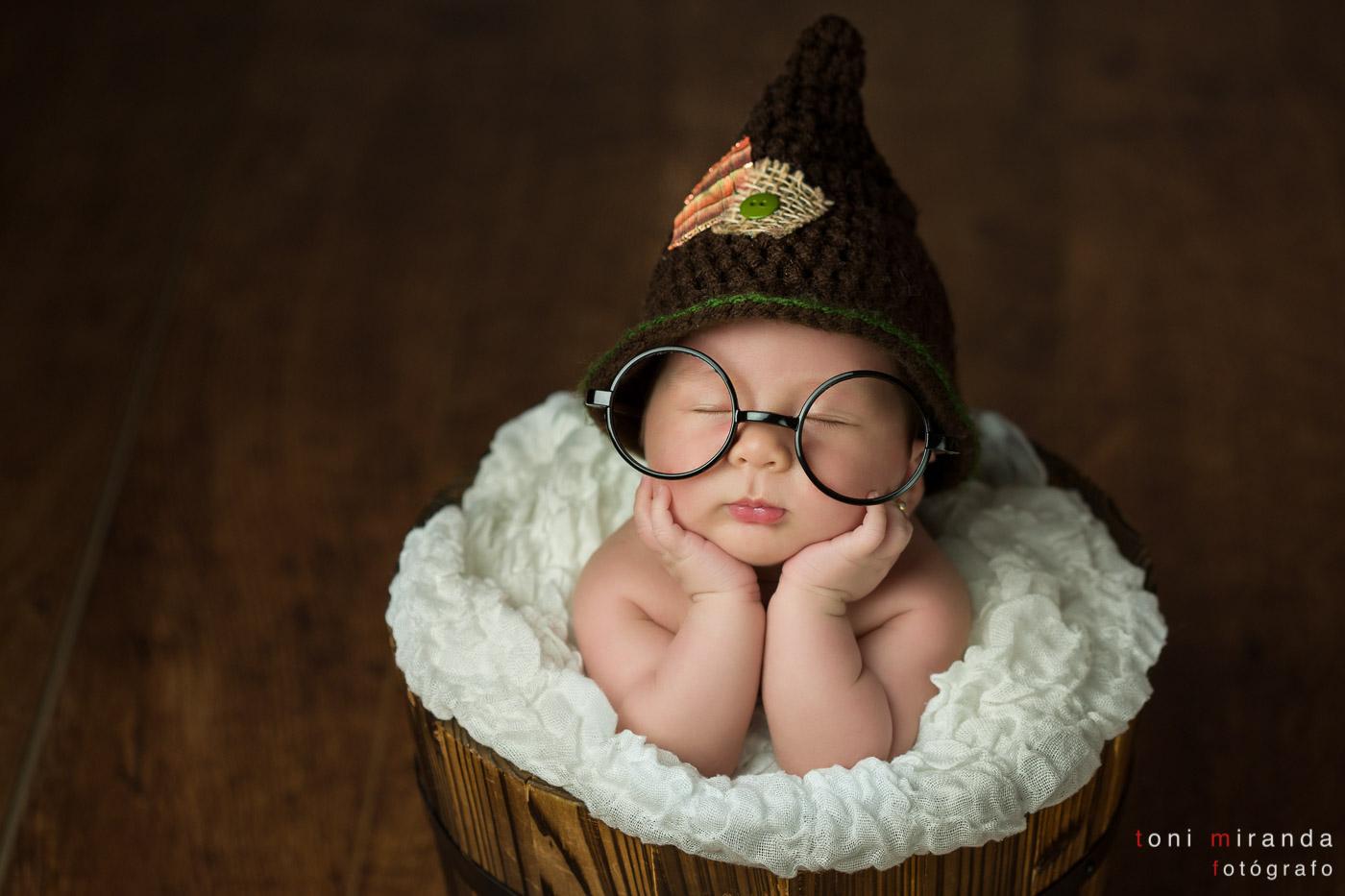 bebe recien nacida con gafas y gorro dentro de cubo