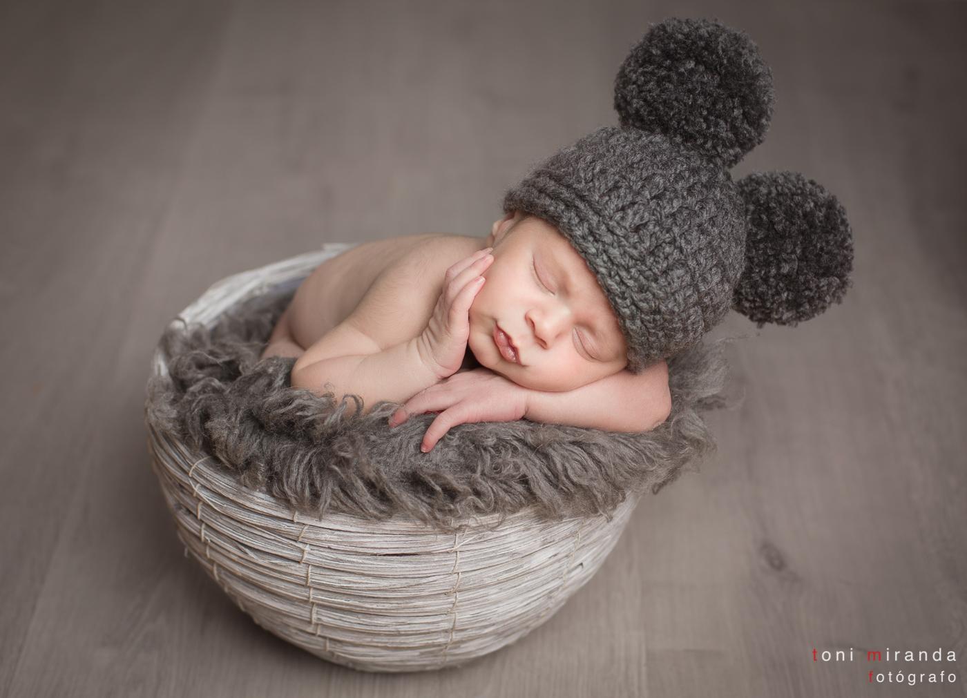 bebe durmiendo en cesta con gorrito pompones