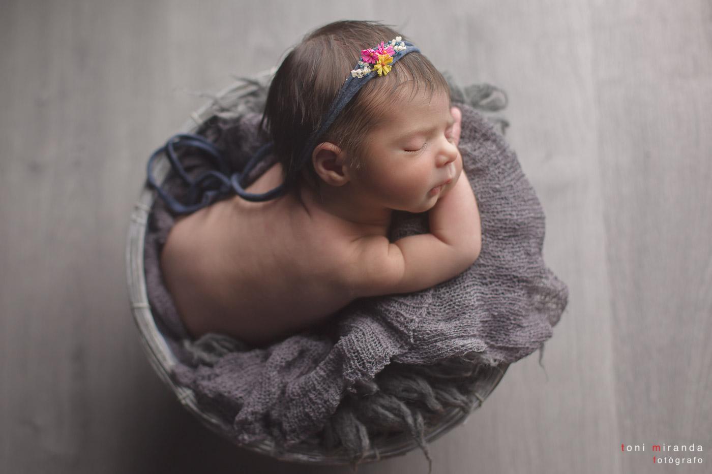 bebe recien nacido durmiendo en cesta con diadema en sesión fotográfica en estudio de alcoy en alicante