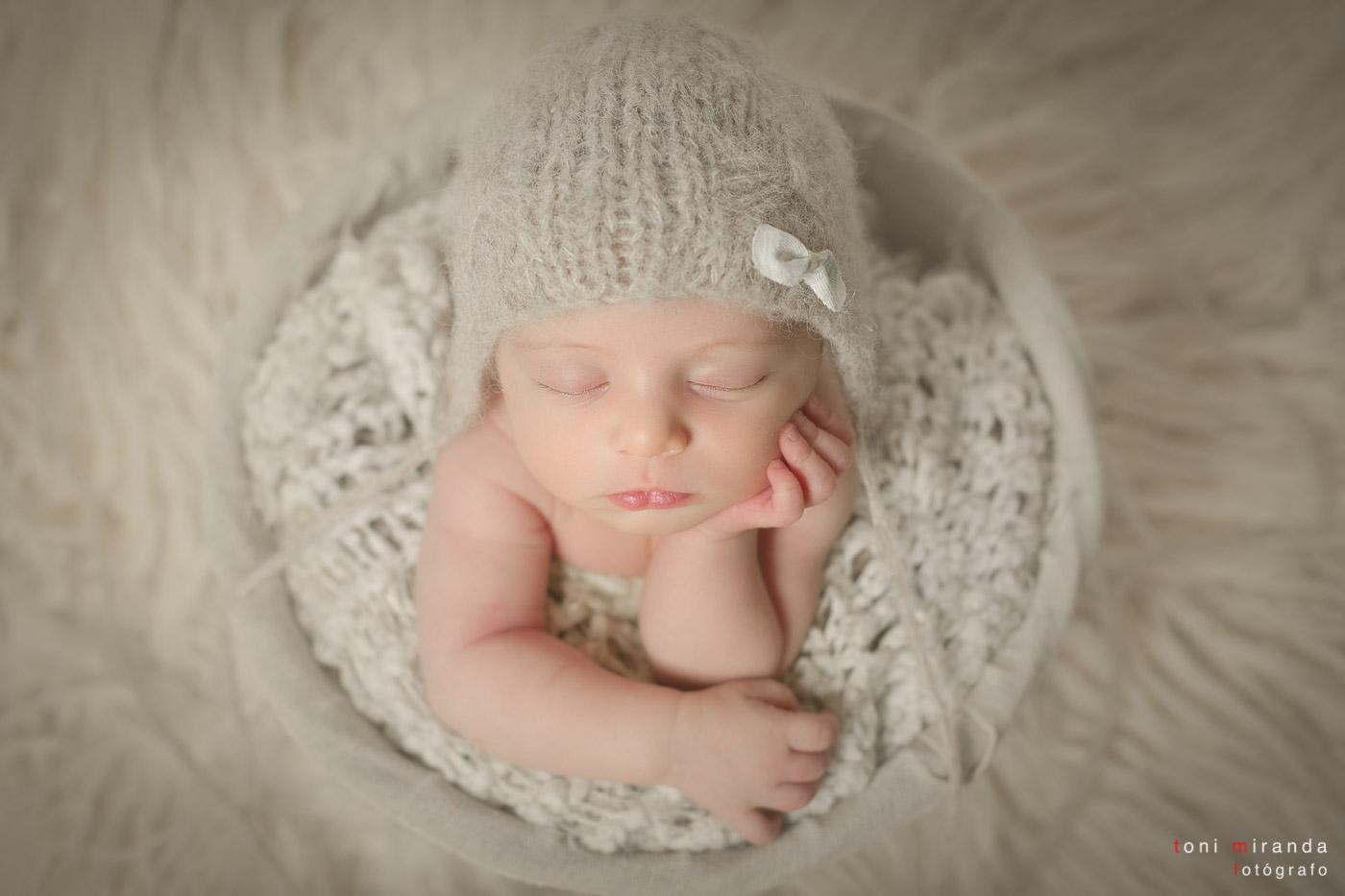 sesión de new born durmiendo dentro de una cesta con gorro de lana en estudio de alcoy de alicante