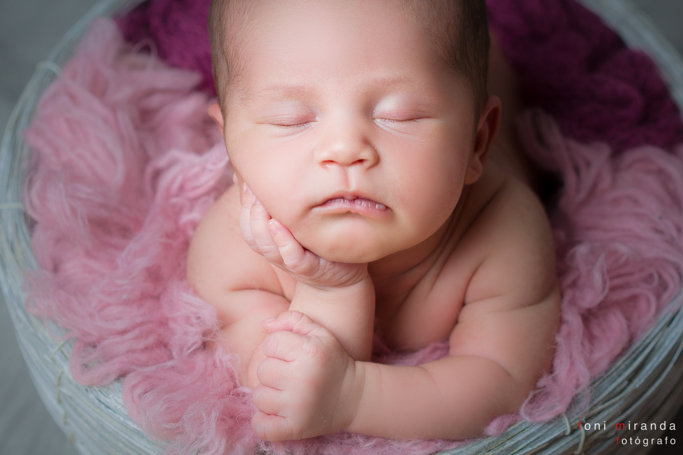 Bebe newborn recien nacido en cesta de mimbre gris en sesion de estudio fotografico Alcoy