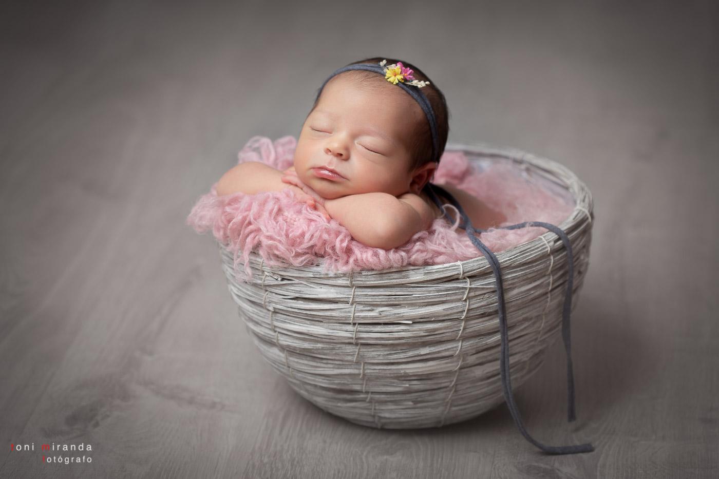bebe durmiendo en cesta con tocado de flores