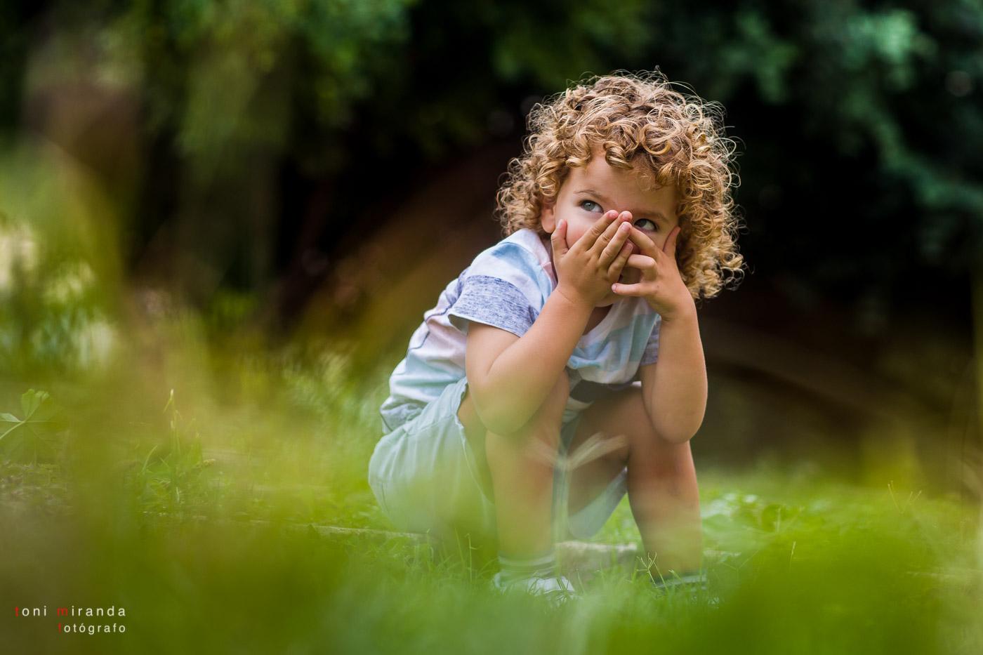 niño rubio de pelo rizado jugando en el parque