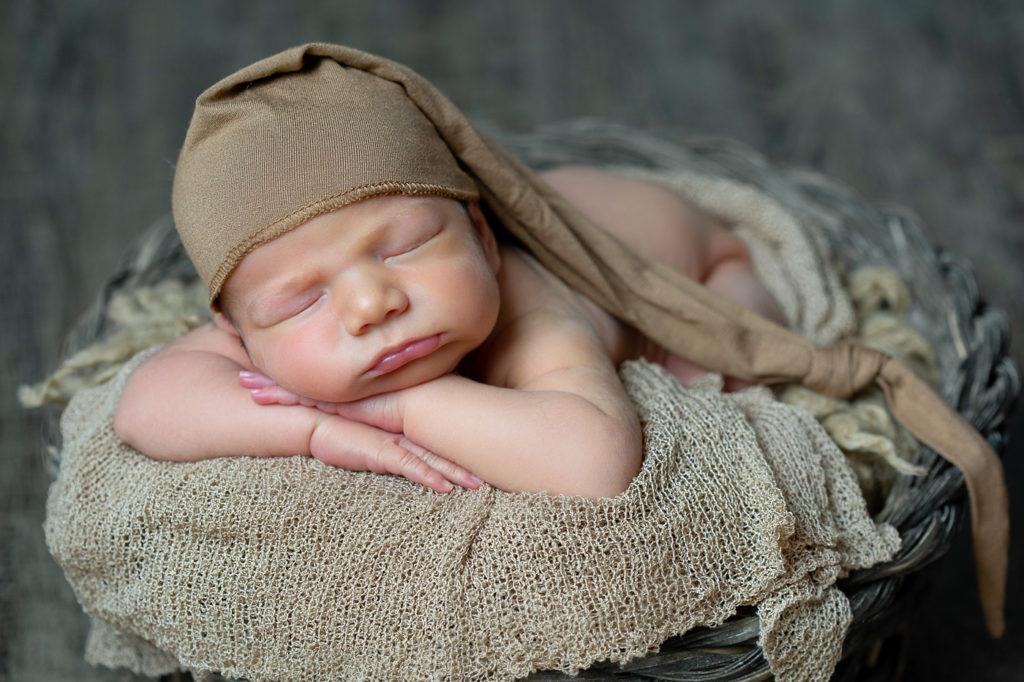 New Born durmiendo en cesta durante sesión fotográfica