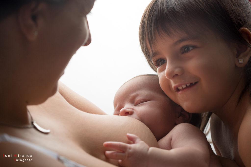 una recien nacida mamando y su hermana mirando a su madre