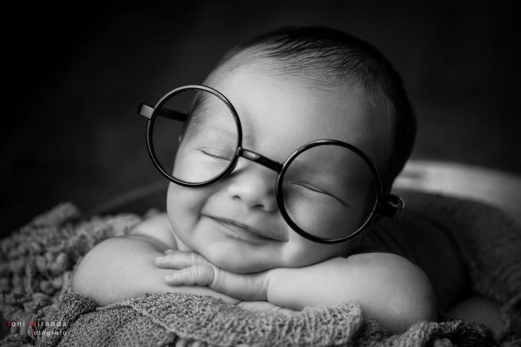 Bebé contento sonriendo con gafas en fotografía en blanco y negro