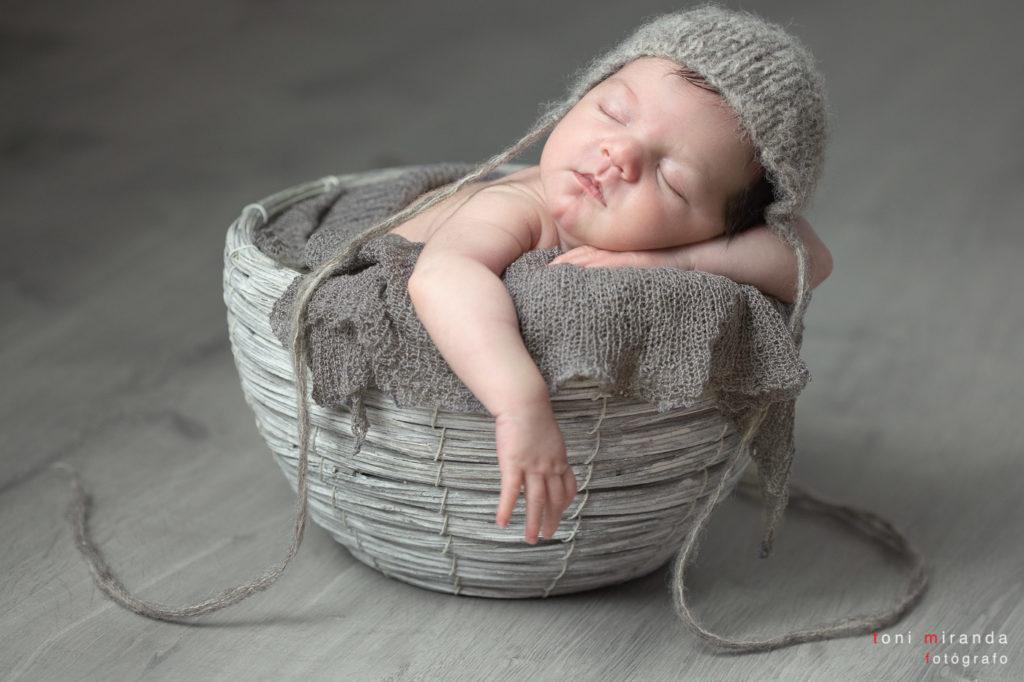 Recien nacido durmiendo en cesta en sesion fotográfica en estudio profesional