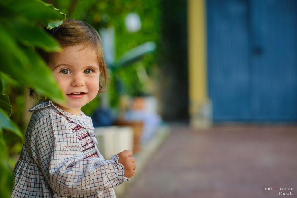 niña sonriendo con vestido a cuadros en parque