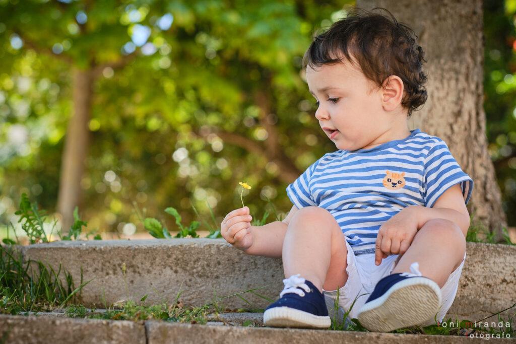 bebe jugando con flores en parque