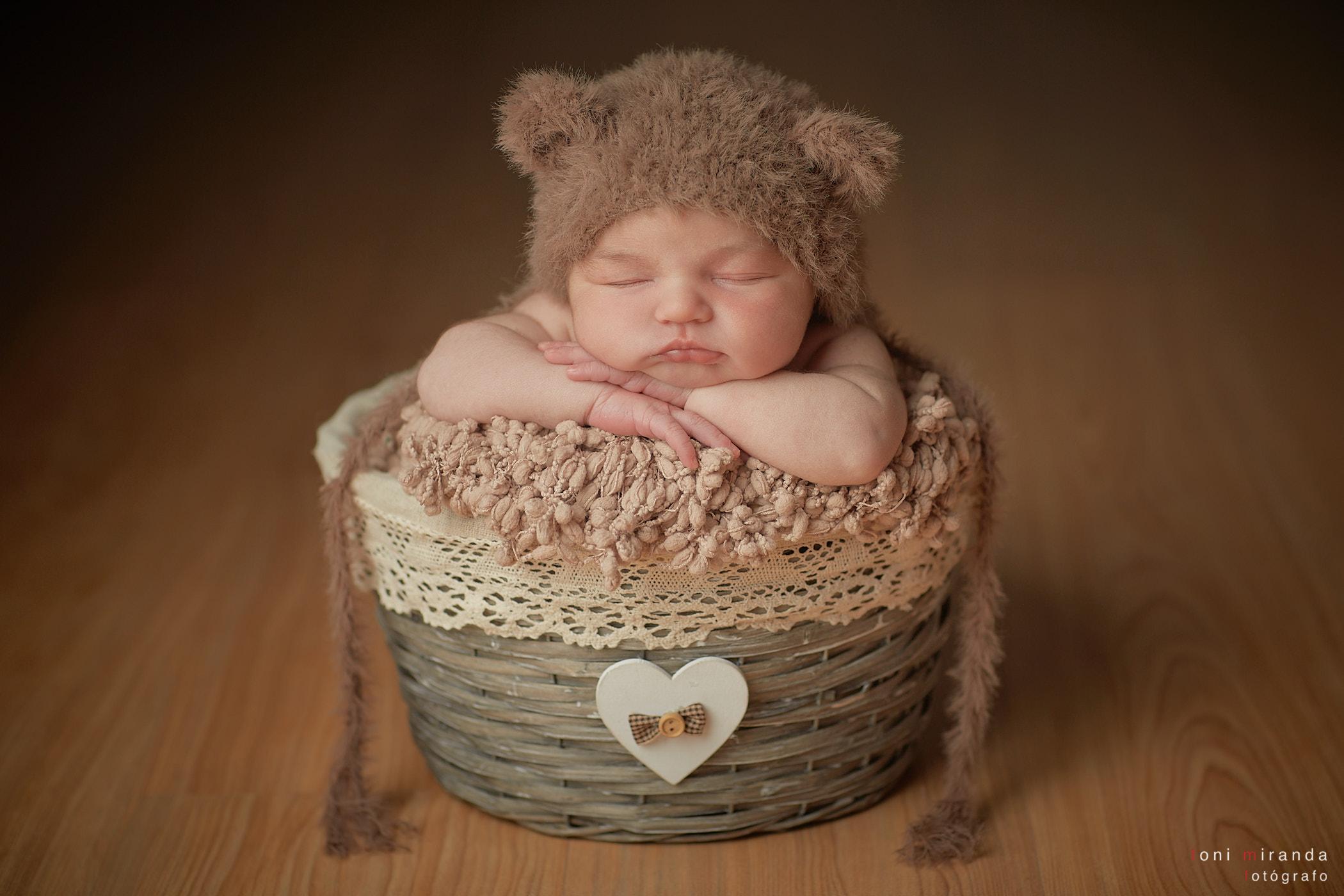 bebe durmiendo dentro de cestita con gorro lana