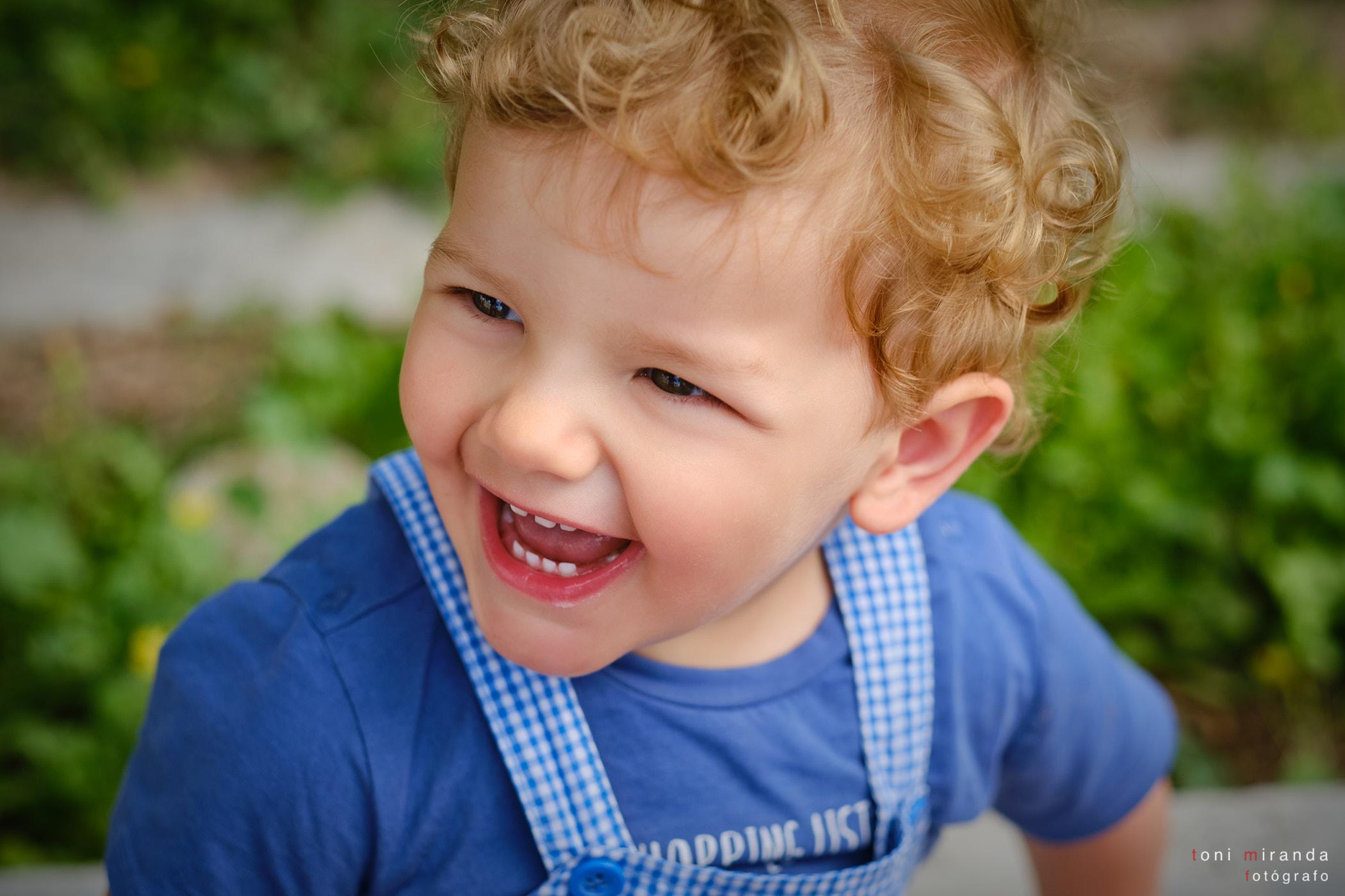 niño rubio pelo rizado sonrisa en el parque