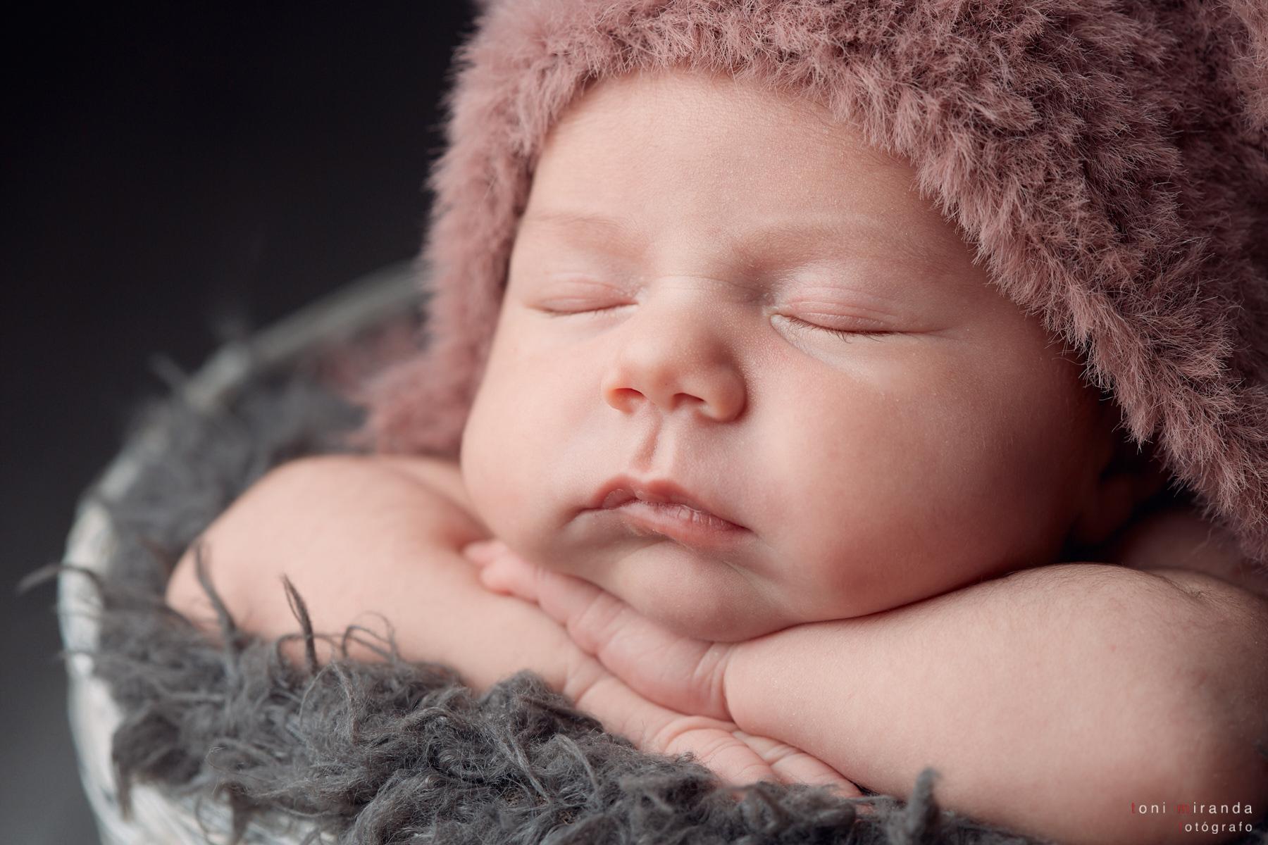Bebé recién nacido durmiendo en cestita