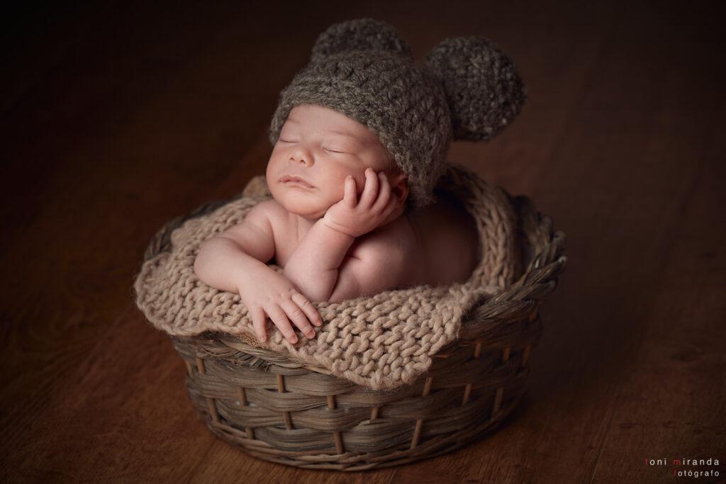 bebe en cesta durmiendo con gorro de bolas