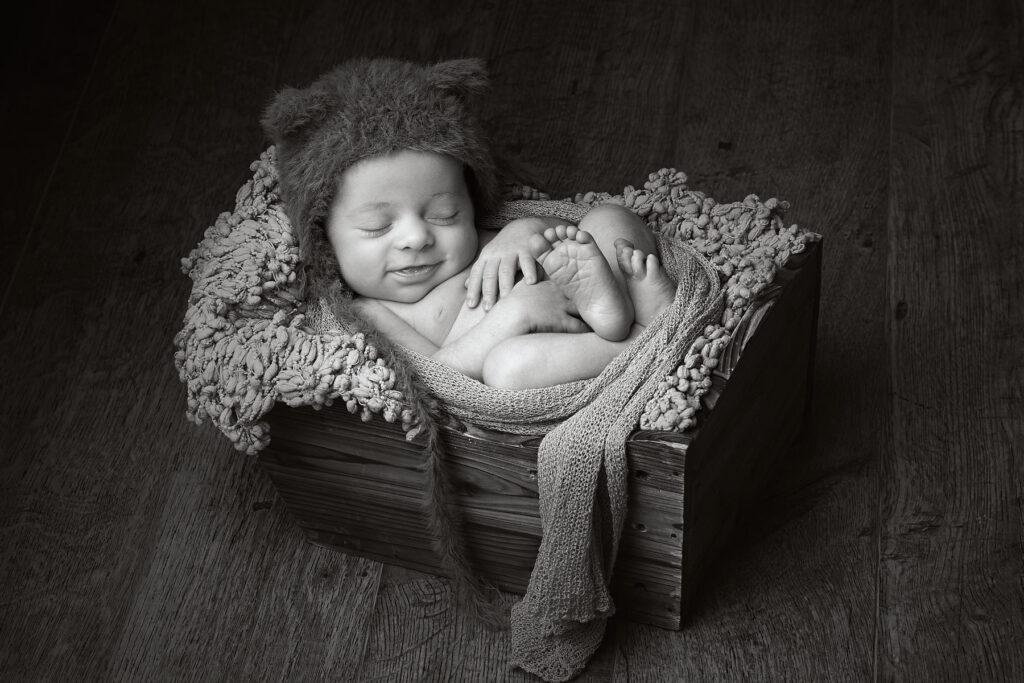 bebe durmiendo en cesta sonriendo