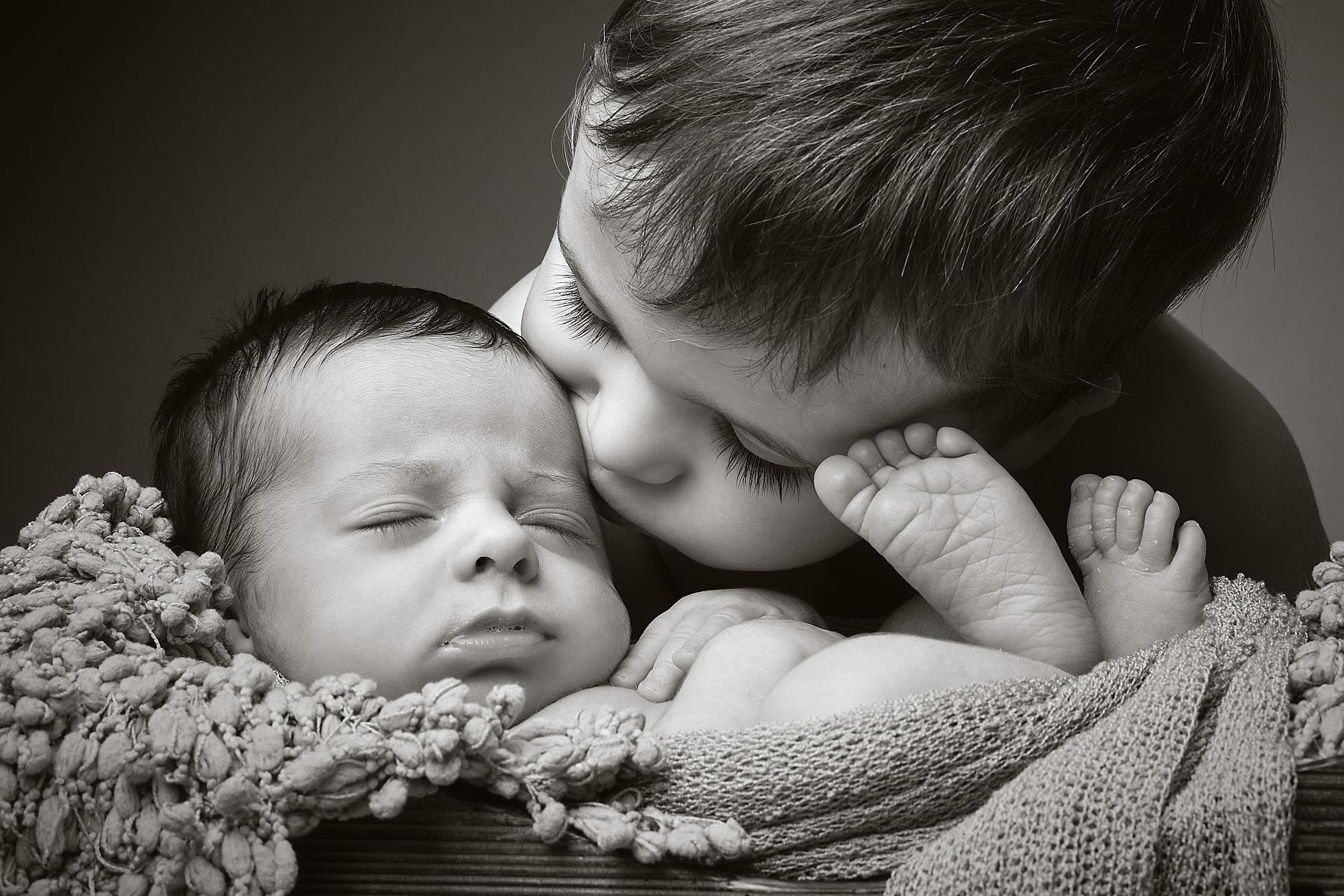 hermano le da un beso al bebe en estudio alcoy