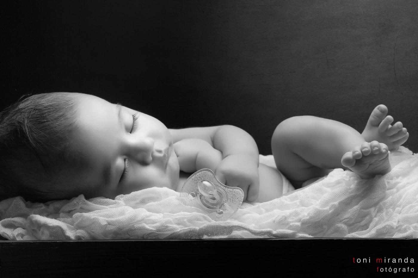 bebe de un mes durmiendo en cuna de madera con chupete