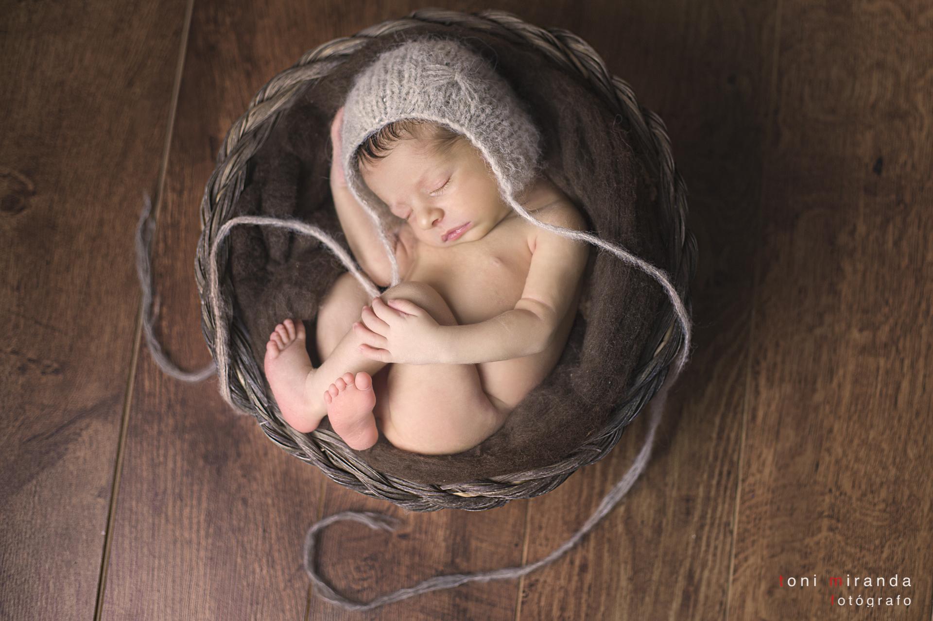 recien nacido metido en cesta en reportaje de newborn