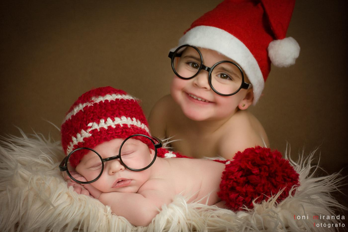 bebe recien nacido con su hermana en foto tipica de navidad