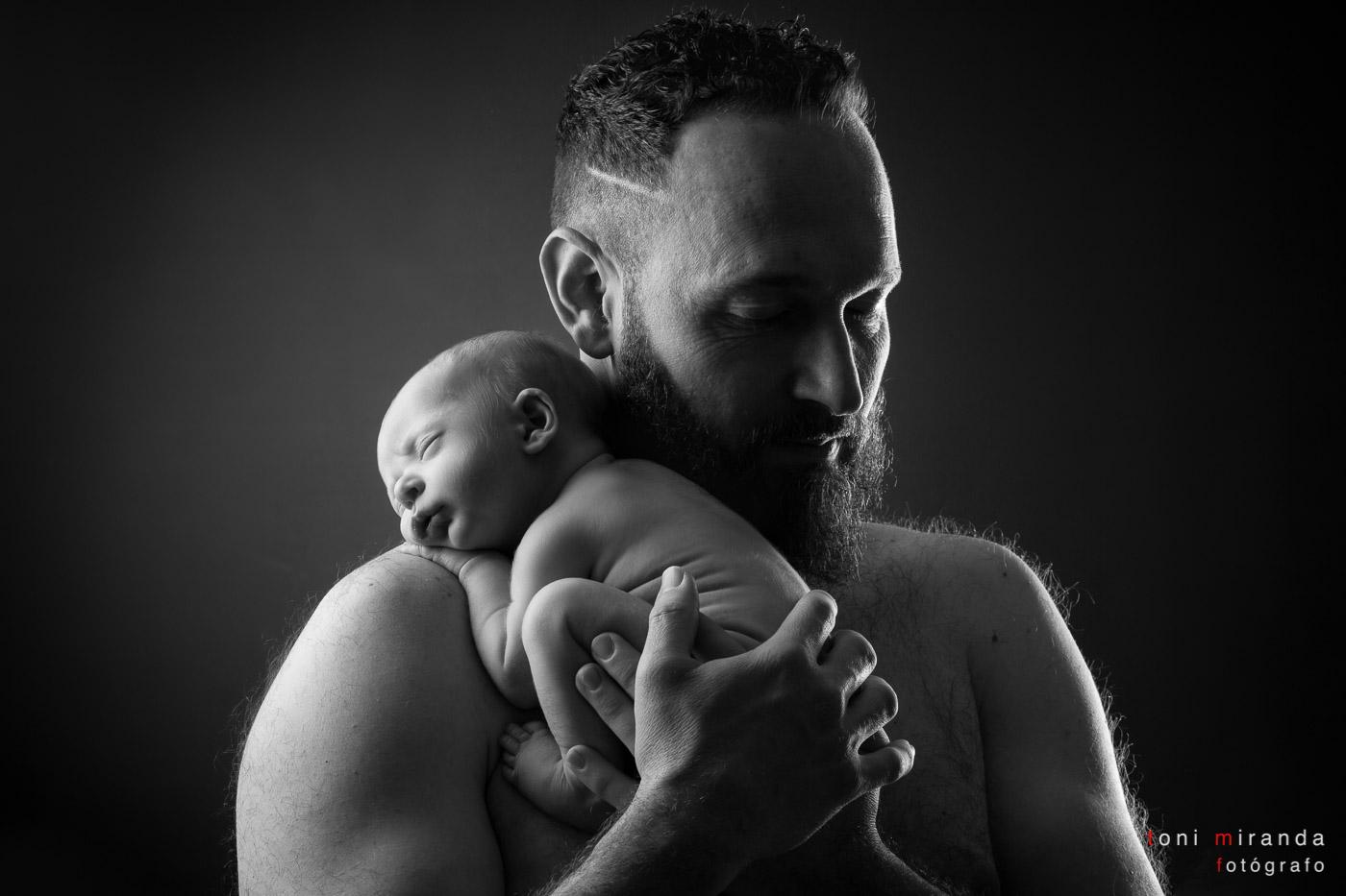 Papá junto a su bebé recien nacido en sesión de estudio
