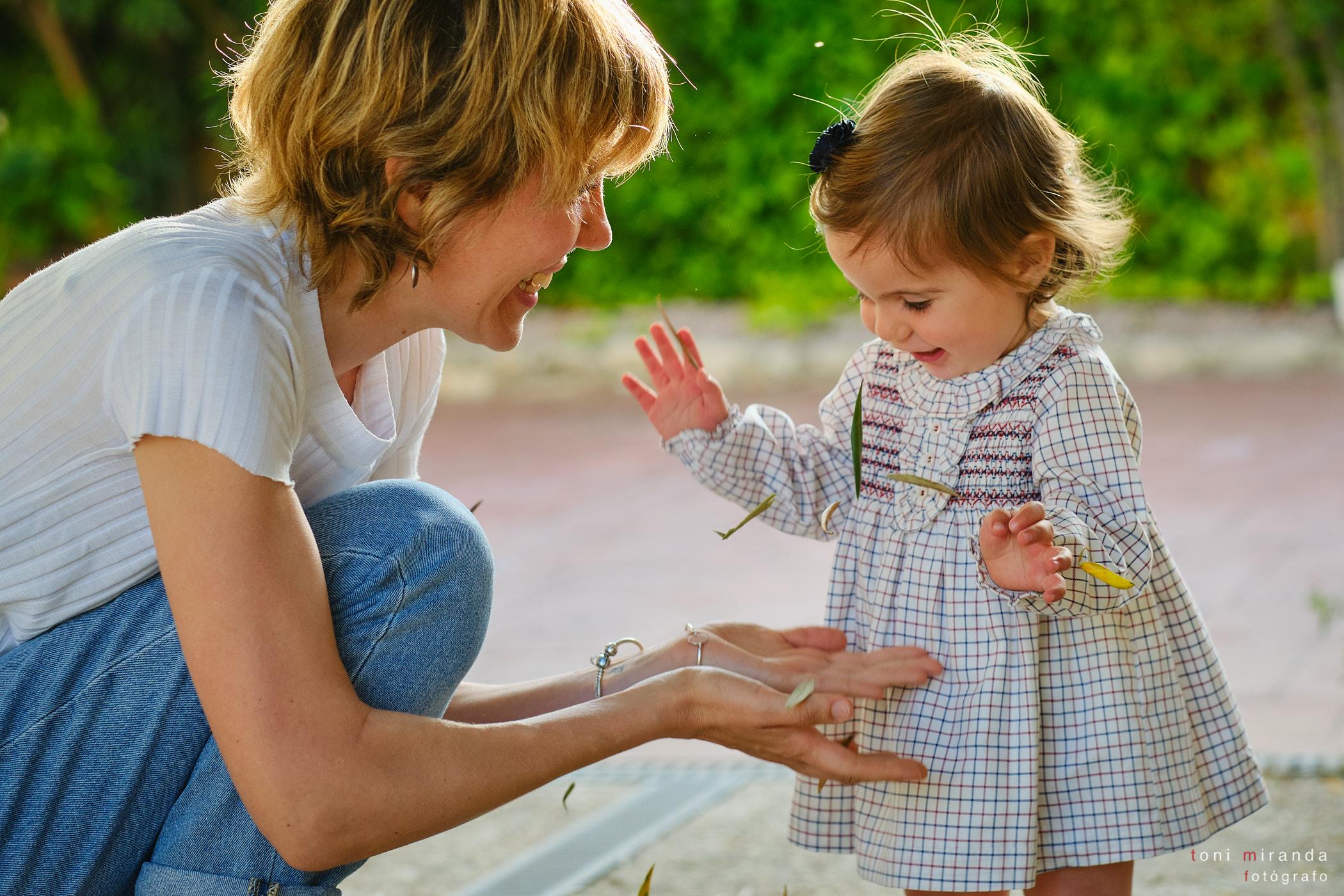 niña riendo en el parque con su madre