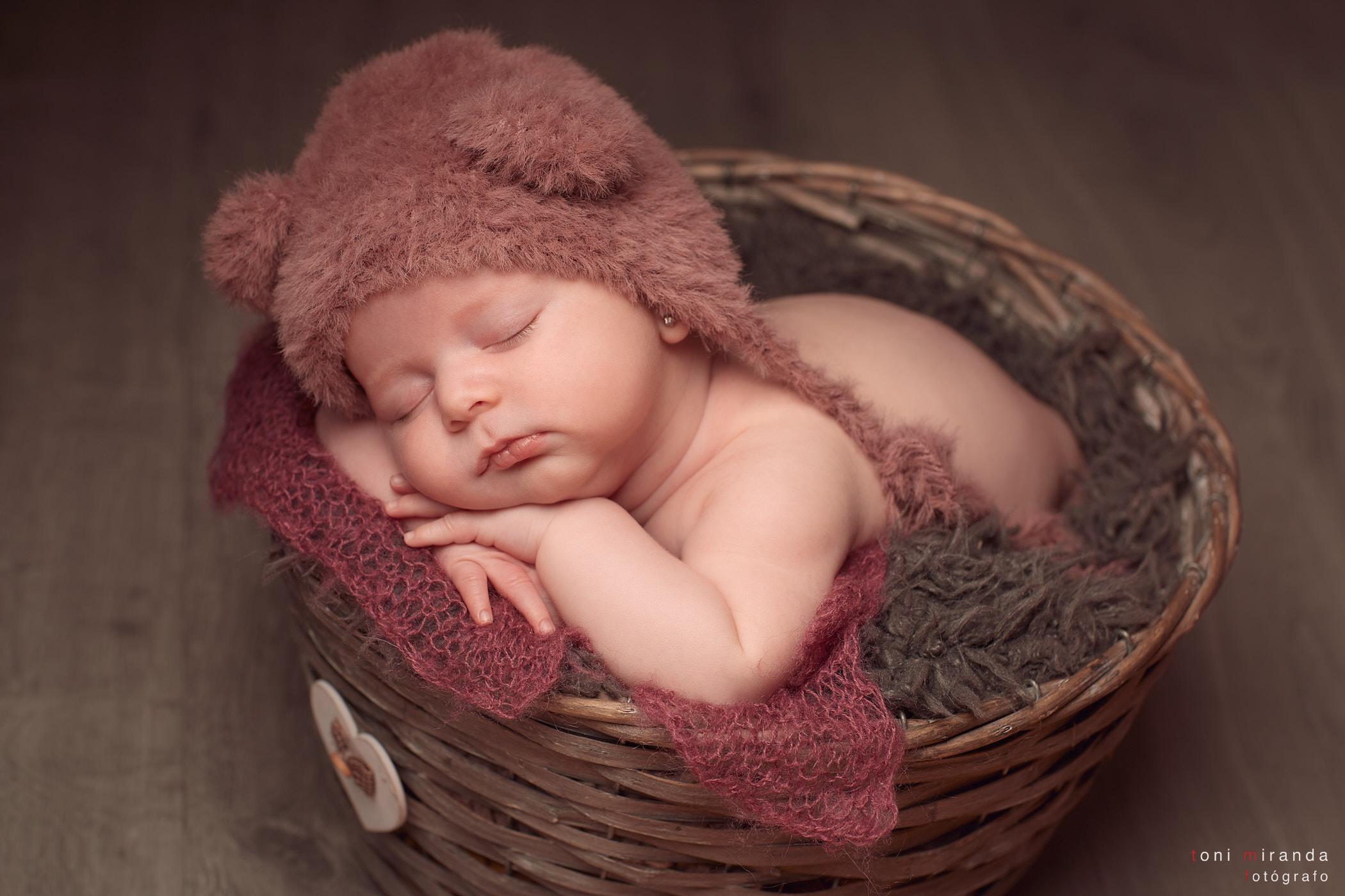 bebe durmiendo en cesta con gorro rosa