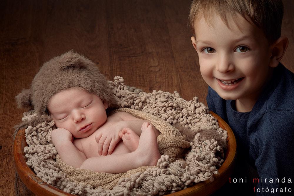bebe durmiendo en cesta con su hermano mayor