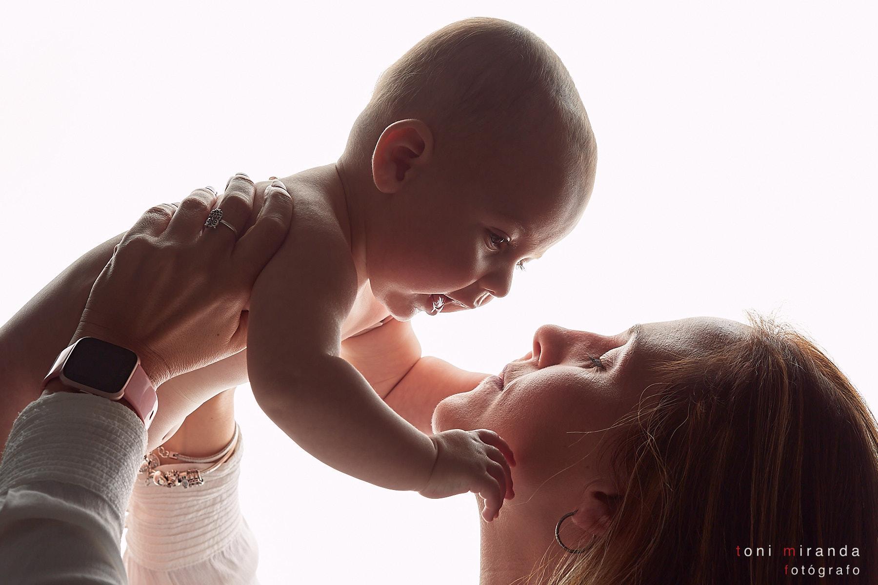 Mamá levantando a su bebé por el aire